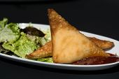 stock photo of samosa  - Two samosas and salad in black background - JPG