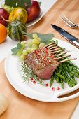 stock photo of crust  - Herb crusted rack of lamb garnished with asparagus green grapes and pomegranates - JPG