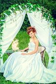 picture of wedding arch  - Beautiful bride with chaming red hair sitting under the wedding arch - JPG