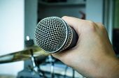 stock photo of karaoke  - Close up of hands holding a microphone (microphone, karaoke, music ) ** Note: Soft Focus at 100%, best at smaller sizes - JPG