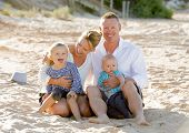 image of couple sitting beach  - young happy family couple and children sitting on beach sand smiling with blond small baby boy and sweet lovely little girl in summer tourism and holidays concept - JPG