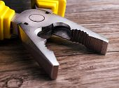 stock photo of pliers  - Close up of a multitool pliers on wooden background - JPG