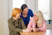 stock photo of reunited  - Close up Three Happy Middle Age Women Friends Enjoying their Girl Talk at the Wooden Dining Table Inside a Restaurant - JPG