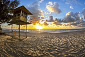 stock photo of coast guard  - Fisheye view of Sunrise over Gold Coast Surfers Paradise beach with lifeguard station - JPG