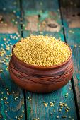 foto of millet  - organic millet seeds in a ceramic bowl on wooden rustic table - JPG