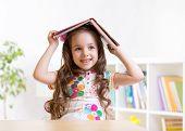 image of preschool  - preschooler  kid girl with book over her head indoors - JPG