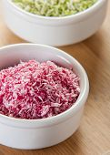 image of naturist  - Unsweetened Coconut Flakes pink close up in white bowl - JPG