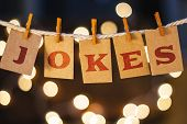 picture of prank  - The word JOKES printed on clothespin clipped cards in front of defocused glowing lights - JPG