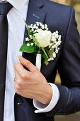 pic of boutonniere  - white rose boutonniere on suit of the groom - JPG