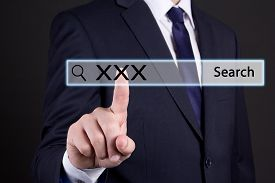 stock photo of pornography  - businessman hand pressing an imaginary button on search bar with xxx text - JPG