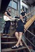 Постер, плакат: Music band outdoor portrait Musicians and woman soloist posing outside against grunge yard image t