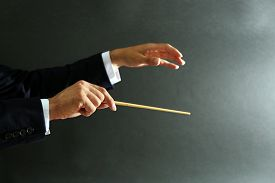 pic of nonverbal  - Music conductor hands with baton on black background - JPG