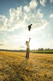 pic of stressless  - Happy Successful Young Businessman Throwing His Coat Up in the Air at the Open Field During Sunset - JPG