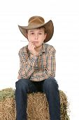Cowboy Sitting On Hay Bale