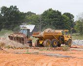 stock photo of oversize load  - bucket loader loading rock into hauler - JPG