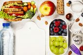 Health & Fitness Food in lunch boxes, measuring tape  and alarm clock on wooden board. Diet food, he poster