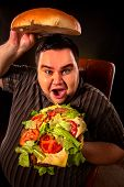 Diet failure of fat man eating fast food hamberger. Overweight person who spoiled healthy food by ea poster