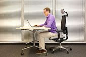 sitting position at workstation. man on chair working with laptop poster