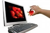 Computer and hand with a strawberry