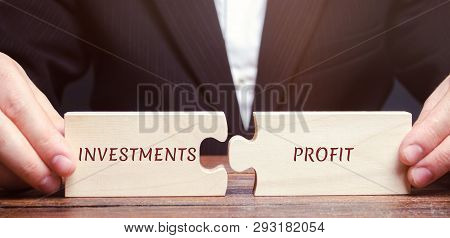 poster of Businessman Collects Puzzles With The Words Investments And Profit. Return On Investment And Investe