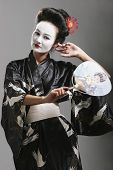 image of japanese woman  - young asian geisha dancing performing whilst holding a fan - JPG