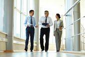 Parceiros de negócios confiante andando no escritório de construção e discutindo o trabalho