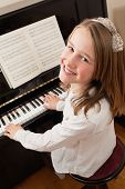 Smiling Girl Playing Her Piano