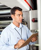 stock photo of blue-collar-worker  - industrial technician taking machine readings - JPG