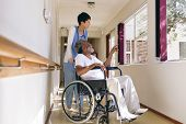 Side view of  Asian female nurse and senior African-american male patient interacting with each othe poster
