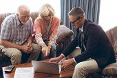 Front view of matured Caucasian male physician and senior Caucasian couple discussing over laptop at poster