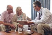 Front view of confident Caucasian male doctor interacting with senior Caucasian couple at retirement poster