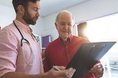 Side view of Caucasian male doctor showing medical report to a Caucasian senior patient in clinic poster