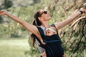 Little Baby Girl And Her Mother Walking Outside Babywearing In The Ergo Carrier Concept poster