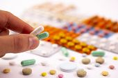 Male Hand Holds Green And White Capsules Above Colorful Pills And Capsules In Plastic Packs - Bliste poster