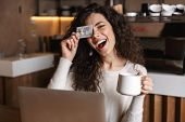 Image of pretty emotional girl sitting in cafe using laptop computer holding credit card. poster