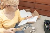 Single Young Woman Assembling Pieces Of New Furniture And Reading The Instruction, Open Boxes With F poster