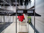 Storage Of Outerwear In The Wardrobe In Public Place. Hangers In Row Cloakroom In Public Building Lo poster