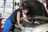 Auto mechanic working on a car in garage