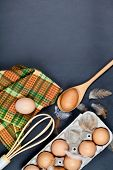 Eggs, kitchen utensil and feathes on backboard background. Eggs, wooden spoon, whisker, towel and ot poster