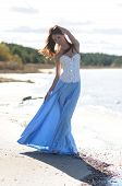 picture of windswept  - Windswept attractive woman in long dress and corset standing on the seashore - JPG