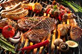 Assorted delicious grilled meat with vegetables sizzling over the coals on barbecue poster