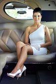Elegant luxury woman sitting in limousine, smiling.?