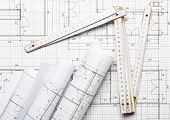 Rolls Of Architectural Blueprint House Building Plans On Blueprint Background With Folding Rule On T poster