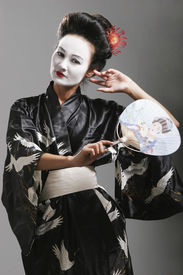 stock photo of japanese woman  - young asian geisha dancing performing whilst holding a fan - JPG