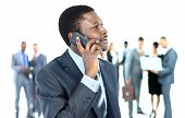 Smiling handsome business man using cell phone with colleagues in background