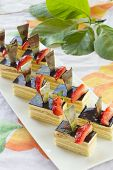 Group Of Mini Square Sponge Cakes With Strawberry And Triangular Chocolate Decoration.