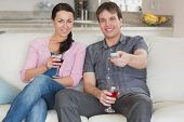 Young couple sitting on the couch in the living room while watching television