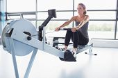 Woman training on row machine in gym