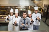 Five workers in restauran with Chef's giving thumbs up