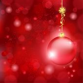 Blurry lights on dark red background and a red bauble hanging with a golden bow. Great backdrop for Christmas themes. Space for your text.